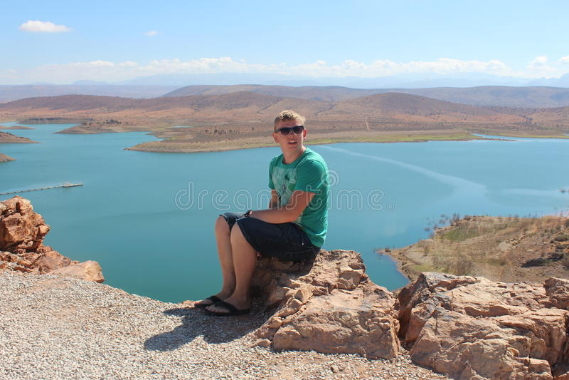 Młody człowiek siedzi na skały i zapory Al massira w Maroko na backgrond obraz royalty free