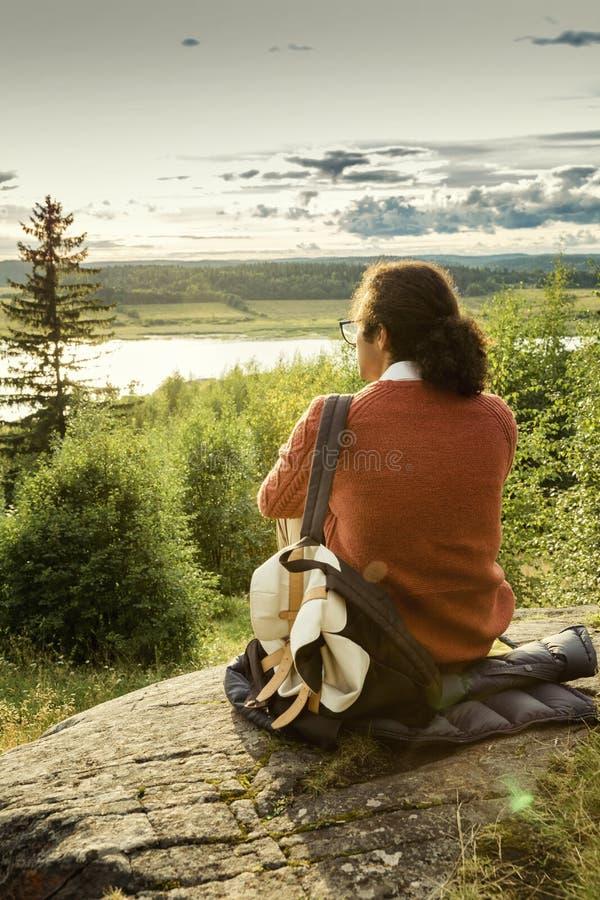 Młody człowiek siedzi na wzgórzu i spojrzeniach przy pięknym krajobrazem zdjęcia stock