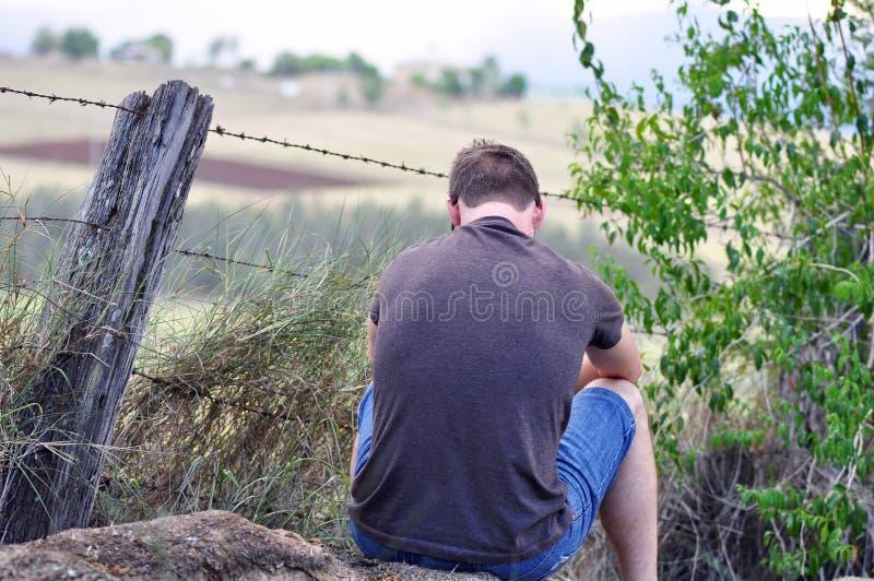 Młody człowiek siedzi samotnego outdoors duszy gmeranie zdjęcie royalty free