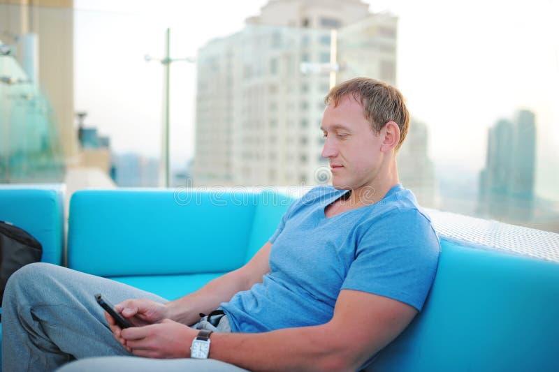 Młody człowiek siedzi w kawiarni i czeka rozkazywać kawę fotografia royalty free