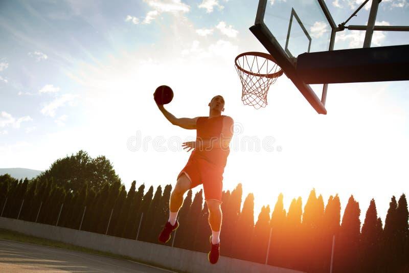 Młody człowiek skacze fantastycznego trzaska wsad bawić się stree i robi zdjęcie royalty free