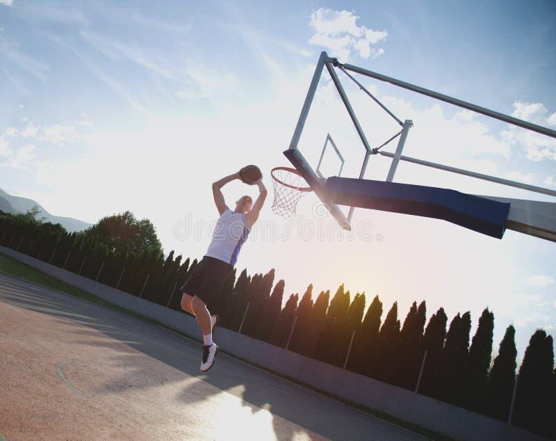 Młody człowiek skacze fantastycznego trzaska wsad bawić się stree i robi zdjęcie stock