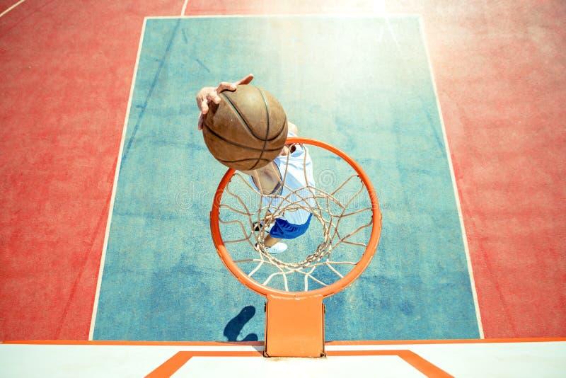 Młody człowiek skacze fantastycznego trzaska wsad bawić się streetball i robi, koszykówka Miastowy autentyczny fotografia royalty free
