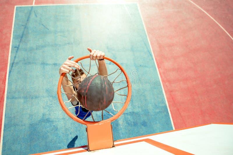 Młody człowiek skacze fantastycznego trzaska wsad bawić się streetball i robi, koszykówka Miastowy autentyczny obraz royalty free