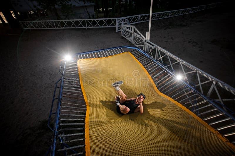 Młody człowiek spada na trampoline na brzeg jeziora zdjęcie royalty free