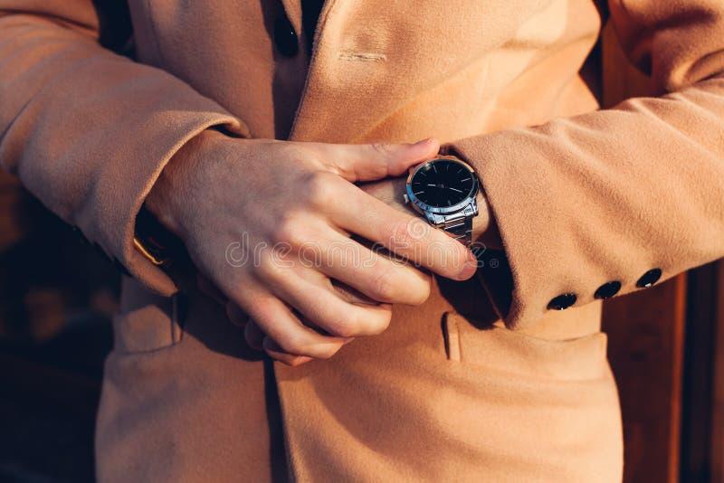 Młody człowiek sprawdza czas na eleganckiego metalu ręki machinalnym zegarku akcesoria męscy obraz royalty free