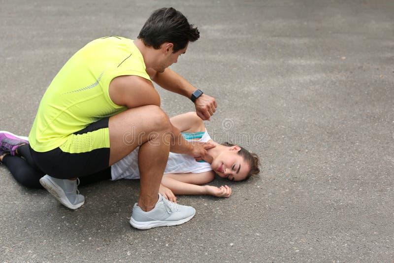 Młody człowiek sprawdza puls nieświadomie na ulicie zdjęcie stock