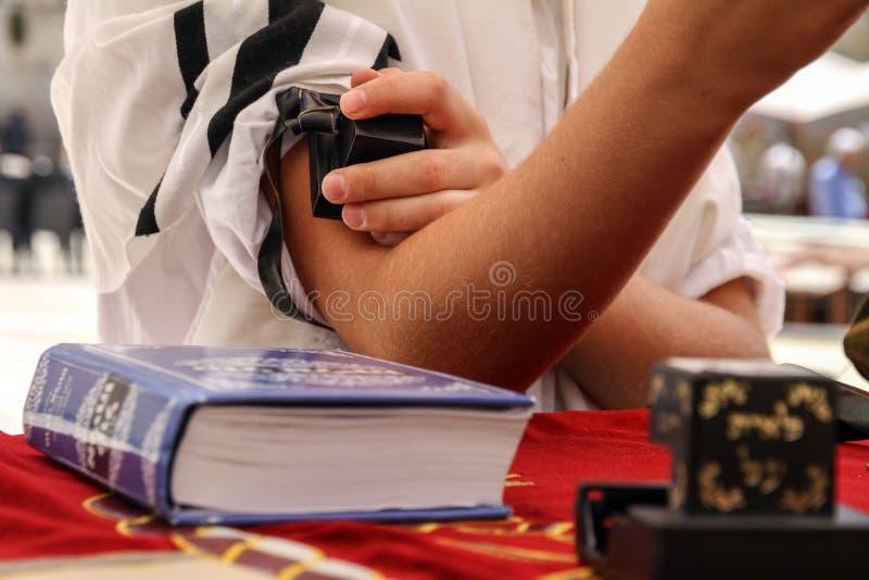 Młody człowiek stawia Żydowskiego Tefillin na jego ręce obrazy royalty free