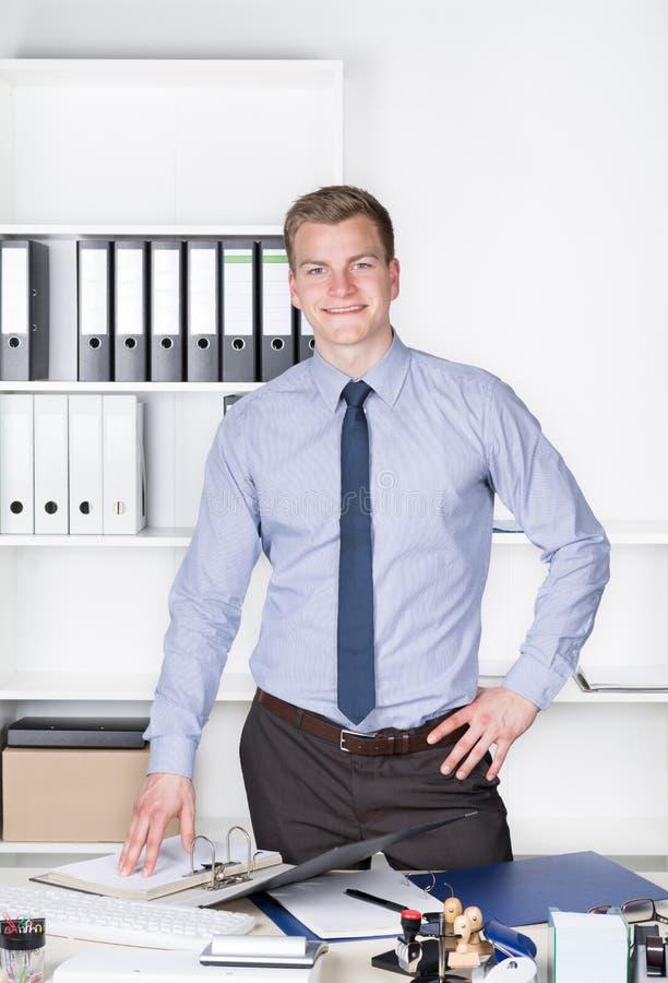 Młody człowiek stoi za biurkiem w biurze zdjęcia stock