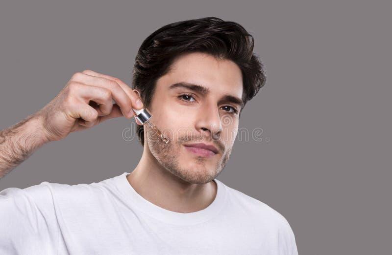 Młody człowiek stosuje organicznie istotnego serum na twarzy obraz stock
