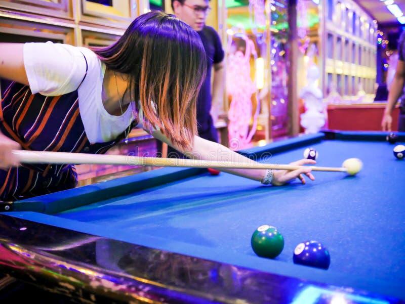 Młody człowiek sztuki billiards w kolorowym klubie - Celować białą piłkę strzał obraz stock
