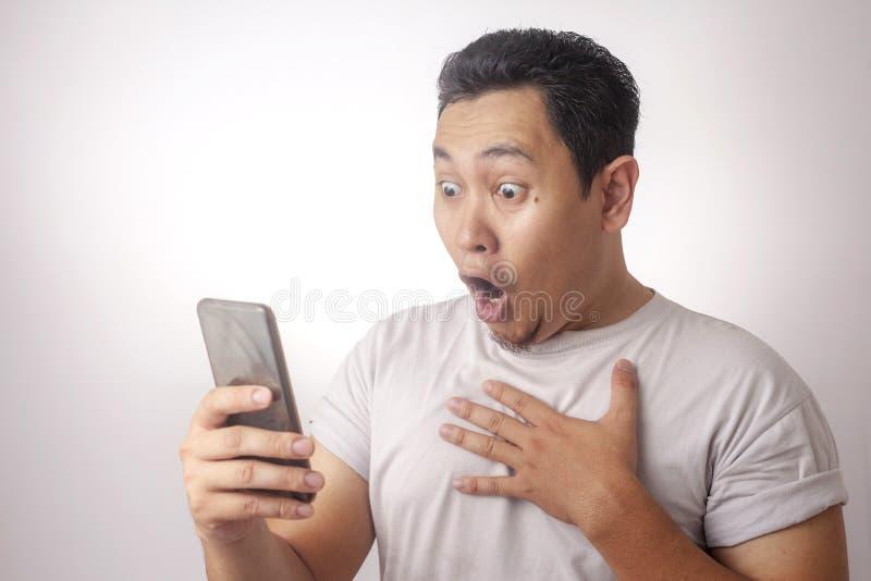 Młody Człowiek Texting Czytelniczego gawędzenie na Jego telefon Zaskakującym gescie fotografia stock