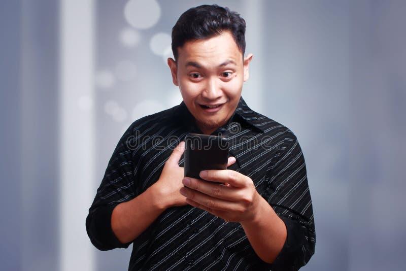Młody Człowiek Texting Czytelniczego gawędzenie na Jego telefonie, ono Uśmiecha się Szczęśliwy obraz stock