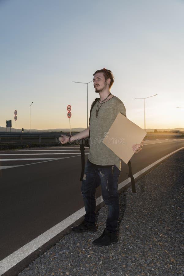 Młody człowiek thumbing na autostradzie obrazy royalty free