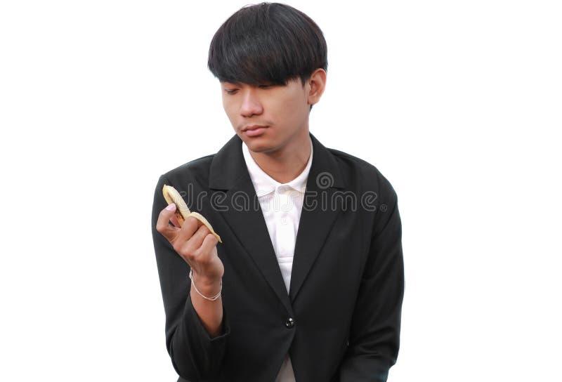 Młody człowiek trzyma banana na białym tle fotografia stock