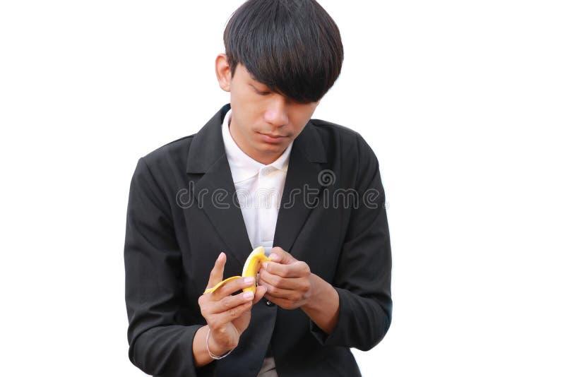 Młody człowiek trzyma banana na białym tle zdjęcia stock