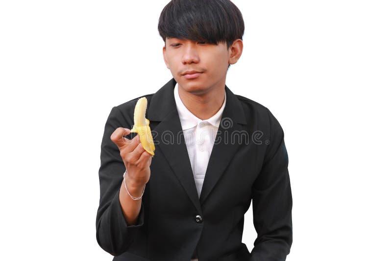 Młody człowiek trzyma banana na białym tle obraz royalty free