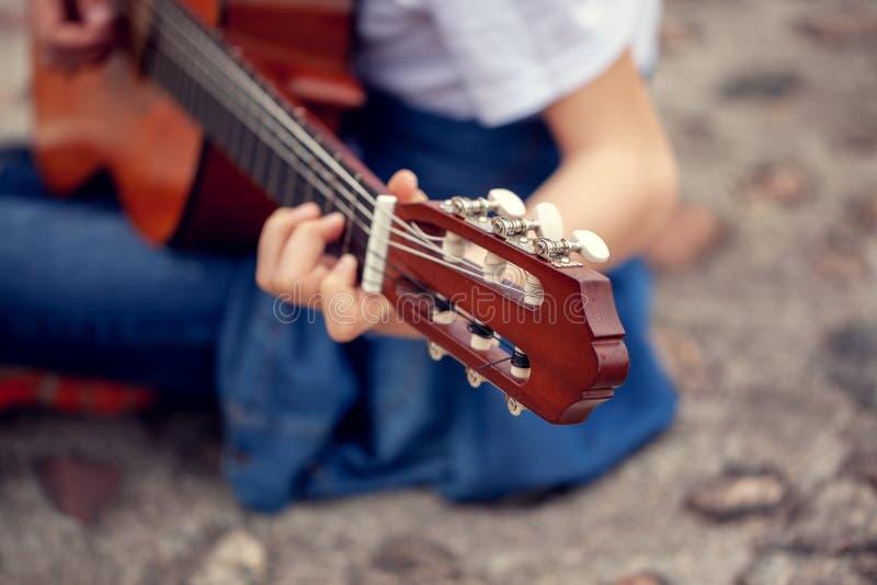 M?ody cz?owiek trzyma gitar? i bawi? si? muzyk? Ostro?? na g?owie sznurek gitara fotografia stock