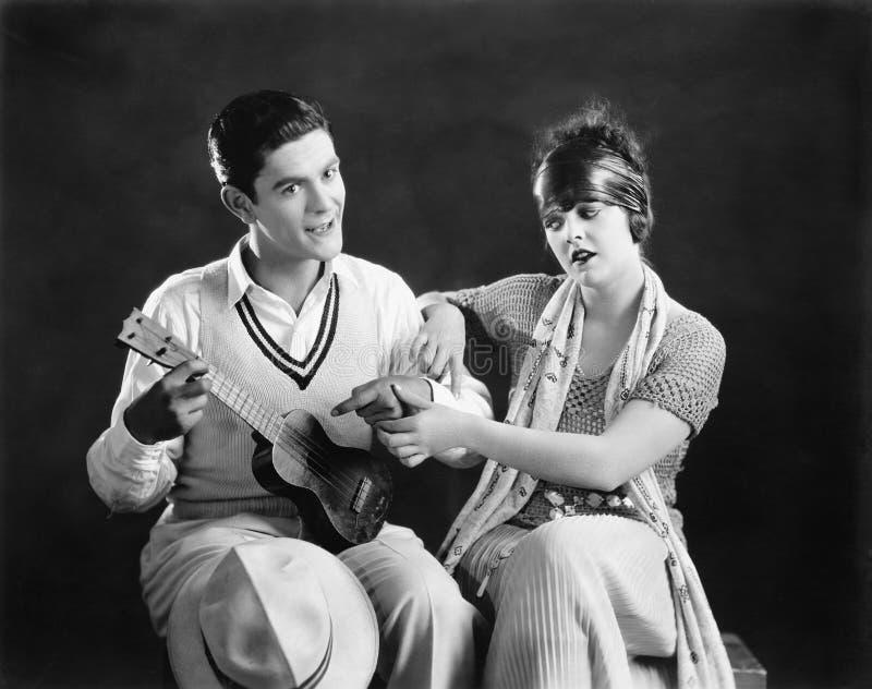 Młody człowiek trzyma gitarę z młodą kobietą uczy on dlaczego bawić się (Wszystkie persons przedstawiający no są długiego utrzyma zdjęcie stock