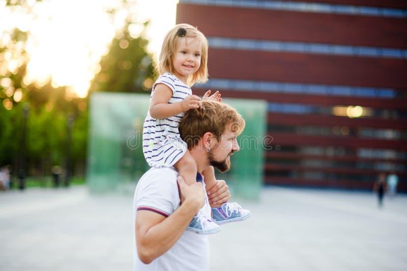 Młody człowiek trzyma jego małej córki na jego ramionach zdjęcie stock