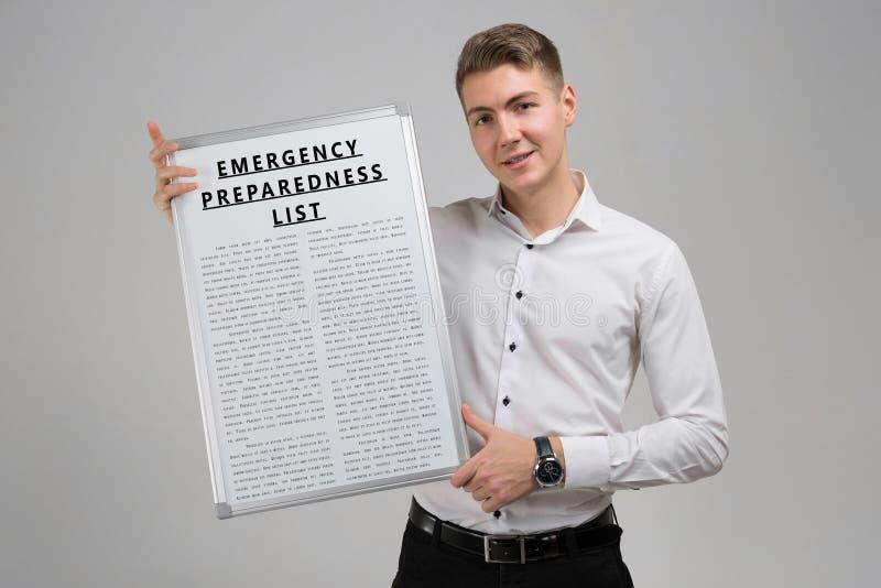 Młody człowiek trzyma listę odizolowywająca na lekkim tle Przeciwawaryjny przygotowanie obraz stock