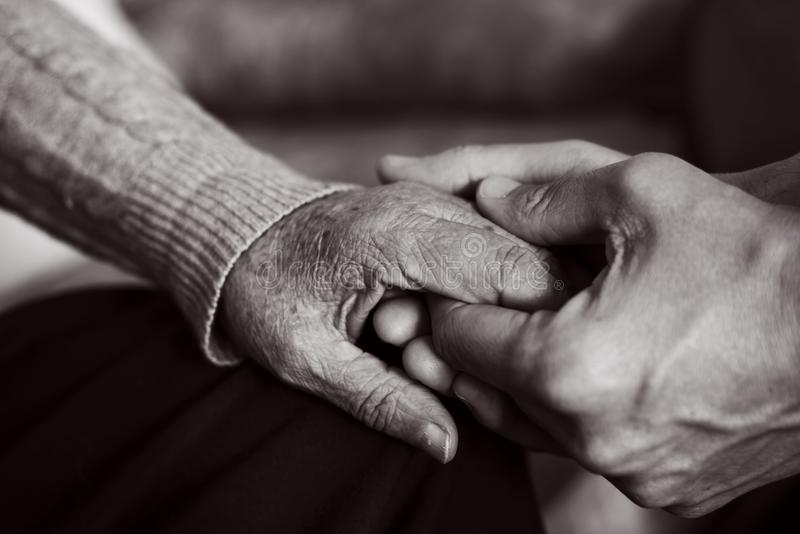 Młody człowiek trzyma rękę stara kobieta zdjęcie stock