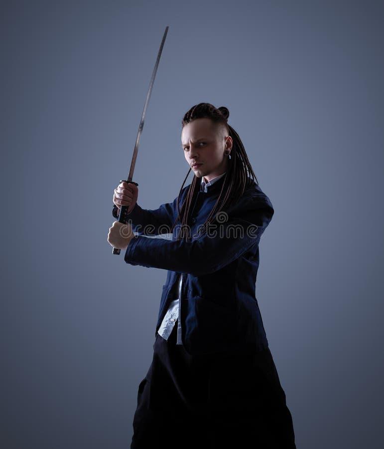 Młody człowiek trzyma samuraja kordzika Splendor fotografia zdjęcie royalty free