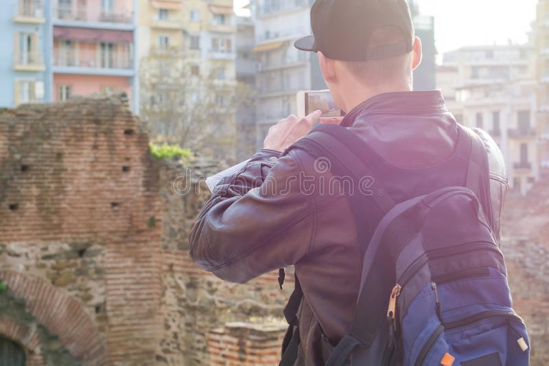 "MÅ'ody czÅ'owiek, turysta, z plecakiem, zdjÄ™cie na smartfonie, paÅ'ac Galeriusa o zachodzie sÅ'oÅ""ca zdjęcia royalty free"