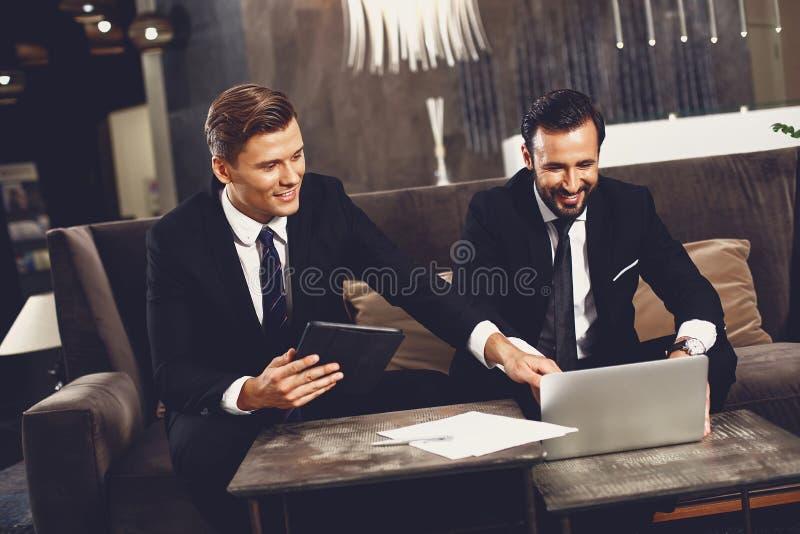 Młody człowiek uśmiecha się i wskazuje na laptopa swojego kolegi obraz stock