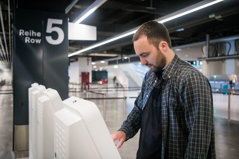 Młody człowiek używa jaźń - odprawa kioski w lotnisku fotografia royalty free