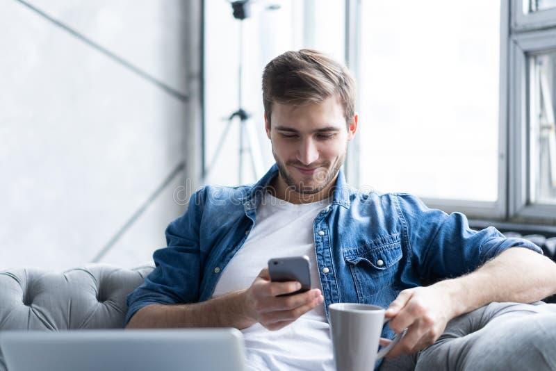 Młody człowiek używa jego smartphone dla online bankowości - siedzący na kanapie z laptopem na skoku zdjęcie stock