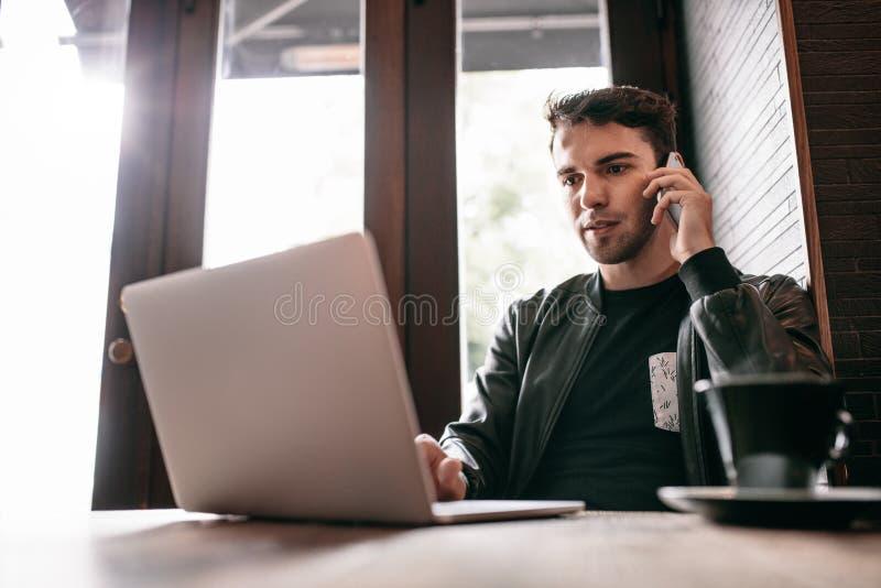 Młody człowiek używa laptop i telefon komórkowego przy kawiarnią zdjęcie royalty free