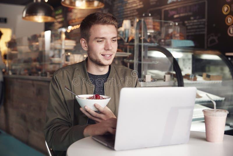 Młody Człowiek Używa laptop W kawiarni Podczas gdy Jedzący śniadanie zdjęcie royalty free