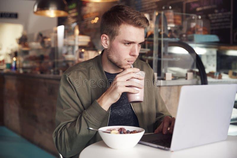 Młody Człowiek Używa laptop W kawiarni Podczas gdy Jedzący śniadanie obrazy royalty free