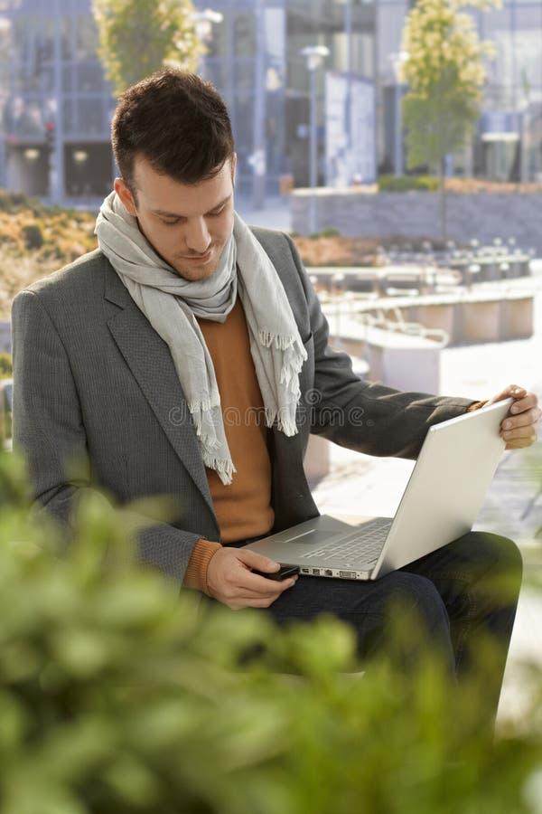 Młody człowiek używa laptop w parku zdjęcia royalty free