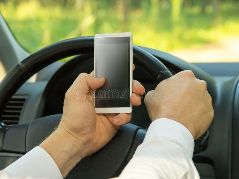 Młody człowiek używa telefon komórkowego, jedzie samochód fotografia royalty free