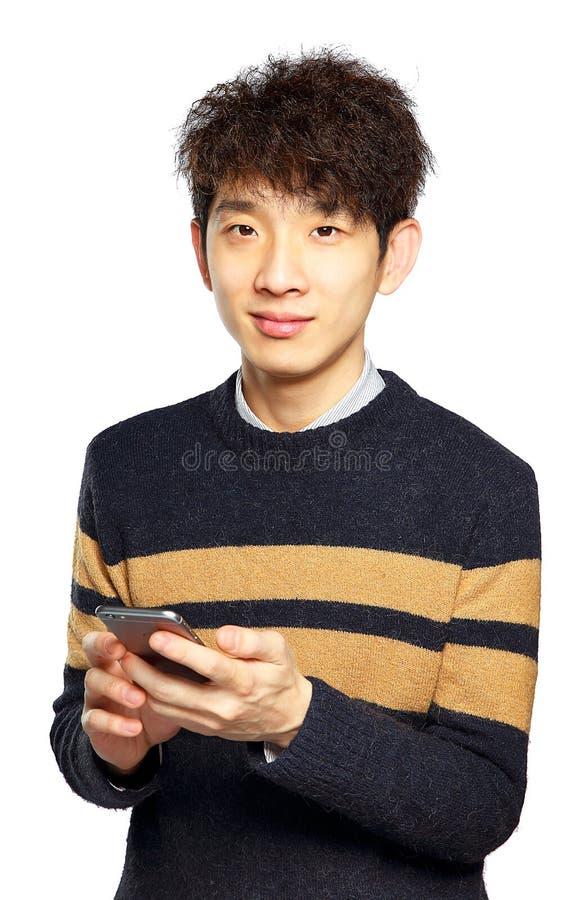 Młody człowiek używa telefon komórkowego na białym tle obraz stock