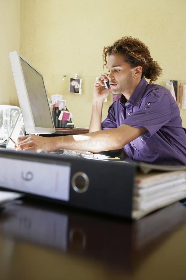 Młody człowiek Używa telefon komórkowego W biurze obrazy stock