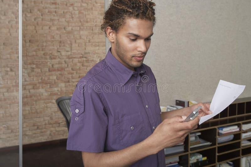 Młody człowiek Używa telefon komórkowego W biurze obraz royalty free
