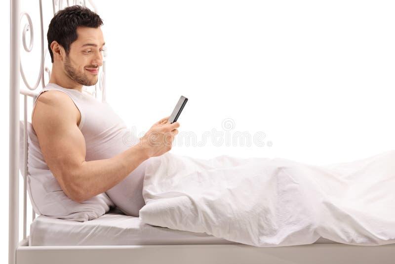 Młody człowiek używa telefon w łóżku podczas gdy kłamający obrazy stock