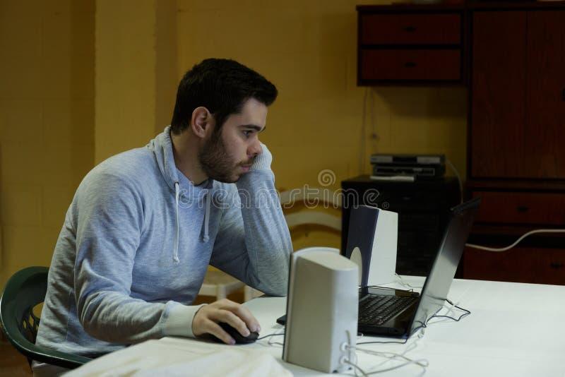 Młody człowiek używa wiszącą ozdobę, pastylkę, laptop i hełmofony jego, zdjęcie stock