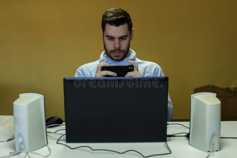 Młody człowiek używa wiszącą ozdobę, pastylkę, laptop i hełmofony jego, fotografia royalty free