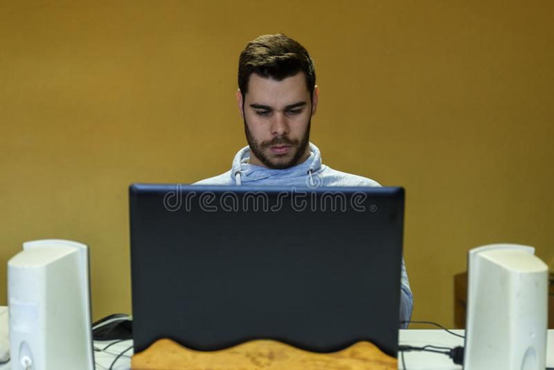 Młody człowiek używa wiszącą ozdobę, pastylkę, laptop i hełmofony jego, zdjęcia royalty free