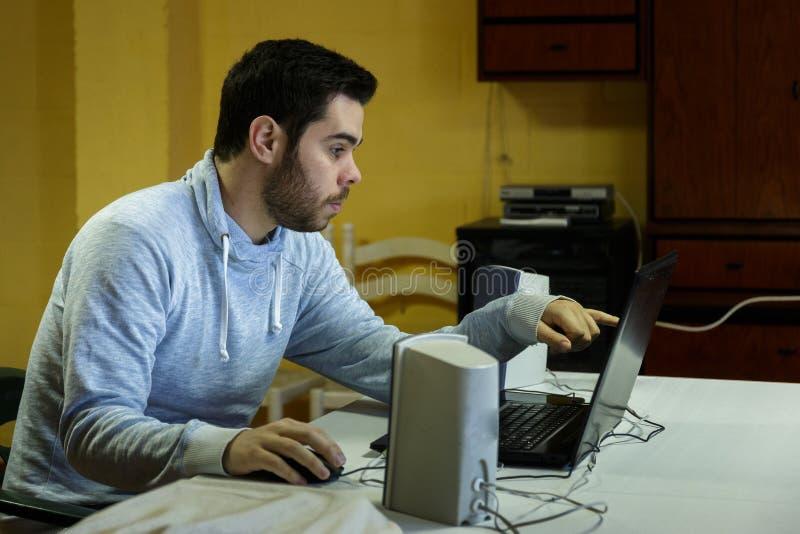 Młody człowiek używa wiszącą ozdobę, pastylkę, laptop i hełmofony jego, obrazy royalty free