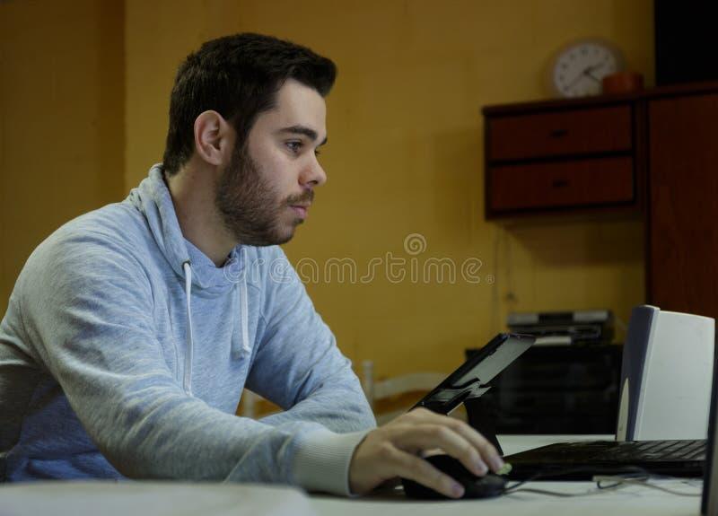 Młody człowiek używa wiszącą ozdobę, pastylkę, laptop i hełmofony jego, zdjęcia stock
