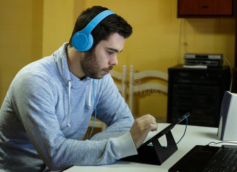 Młody człowiek używa wiszącą ozdobę, pastylkę, laptop i hełmofony jego, obrazy stock