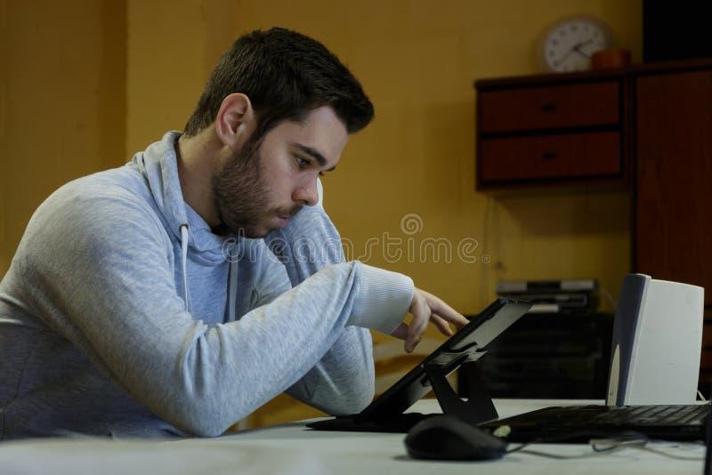 Młody człowiek używa wiszącą ozdobę, pastylkę, laptop i hełmofony jego, obraz stock