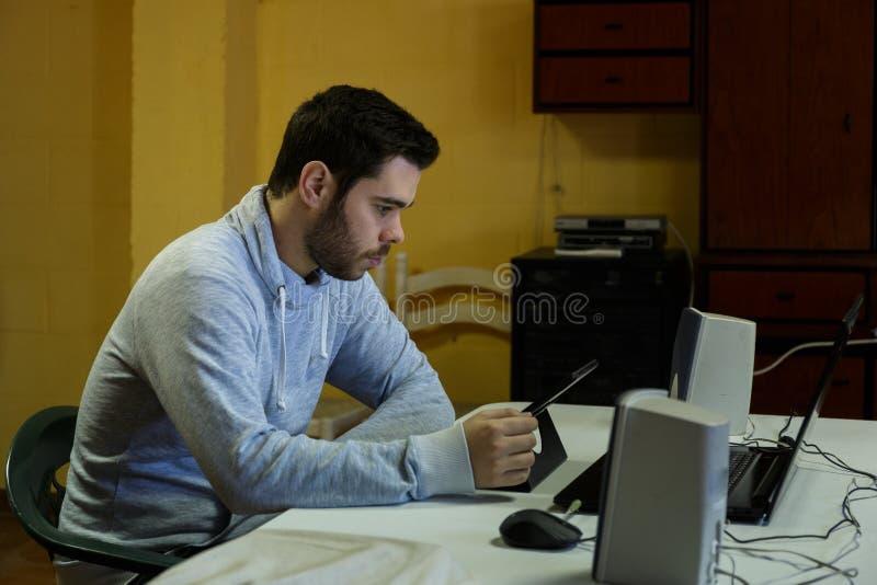 Młody człowiek używa wiszącą ozdobę, pastylkę, laptop i hełmofony jego, fotografia stock