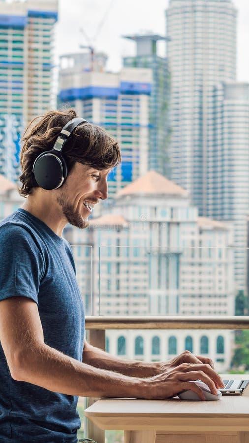 Młody człowiek uczy języka obcego lub uczy się języka obcego na internecie na jej balkonie przeciw tłu zdjęcia stock