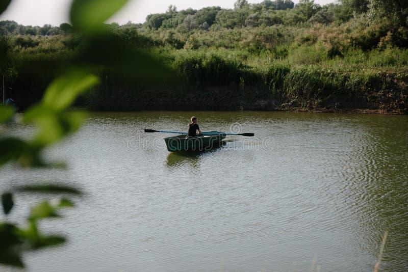 Młody człowiek unosi się na drewnianej łodzi z wiosłami obrazy stock